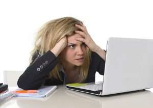 businesswoman with messy hair at her laptop getting frustrated over a bad ad campaign result