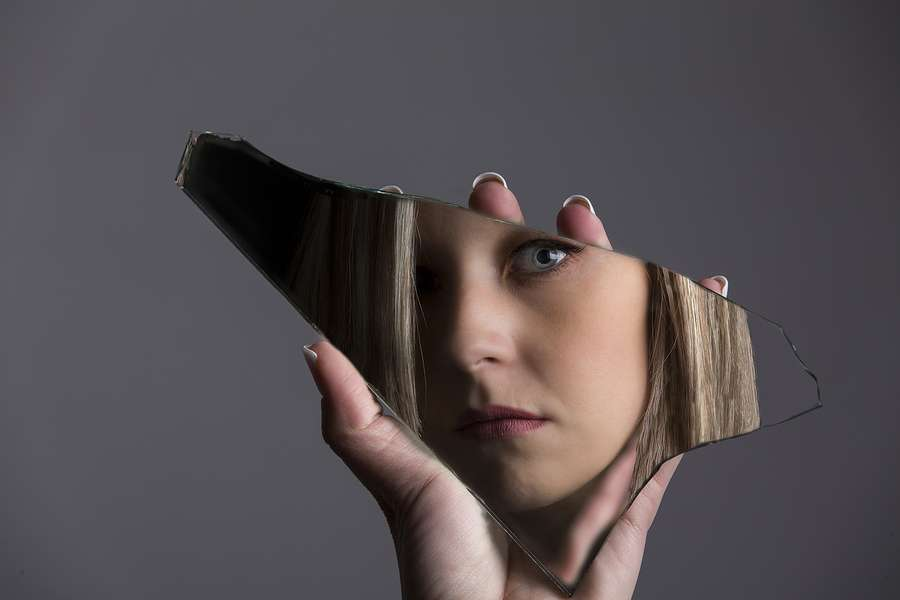 Woman looking at her face in a shard of broken mirror to illustrate measuring keyword rankings in seo